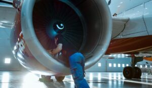 In a Hangar Aircraft Maintenance Engineer/ Technician/ Mechanic Inspects with a Flashlight Airplane's Jet Engine.