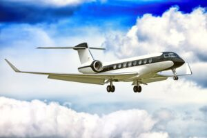 Gulfstream G650 jet engine business corporate private executive luxury jet airplane in black white color flying with aircraft parts gear flaps extended aerial background