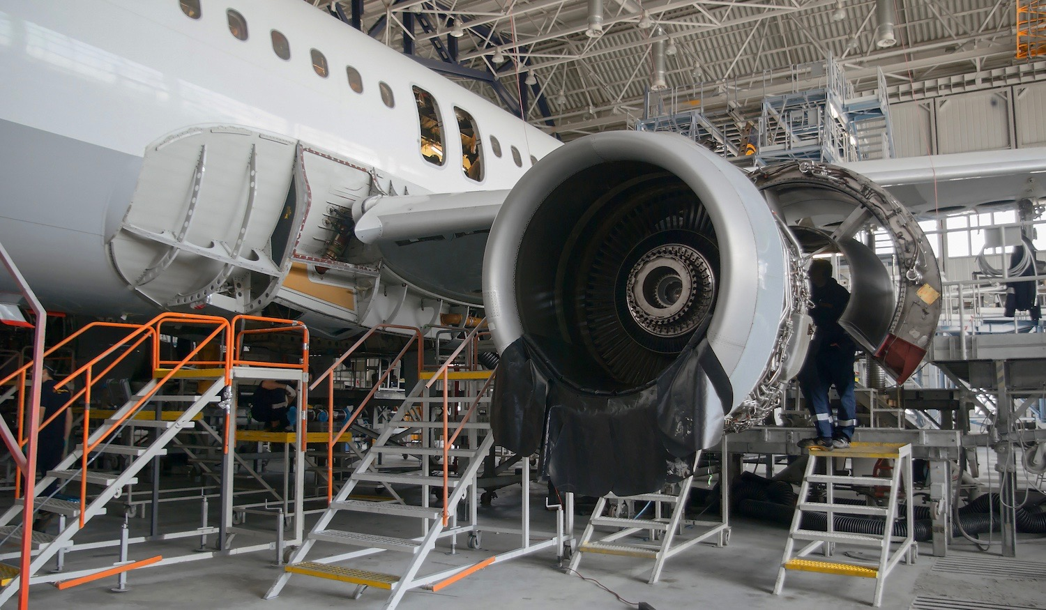 This airplane is disassembled and workers and engineers are seen working during repair and modernisation