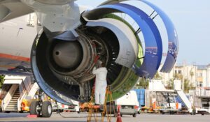 Aircraft technician checking engine of civil airliner