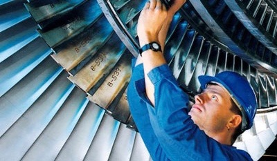 male technician wearing a hard hat in hanger fixing the engine of an aircraft