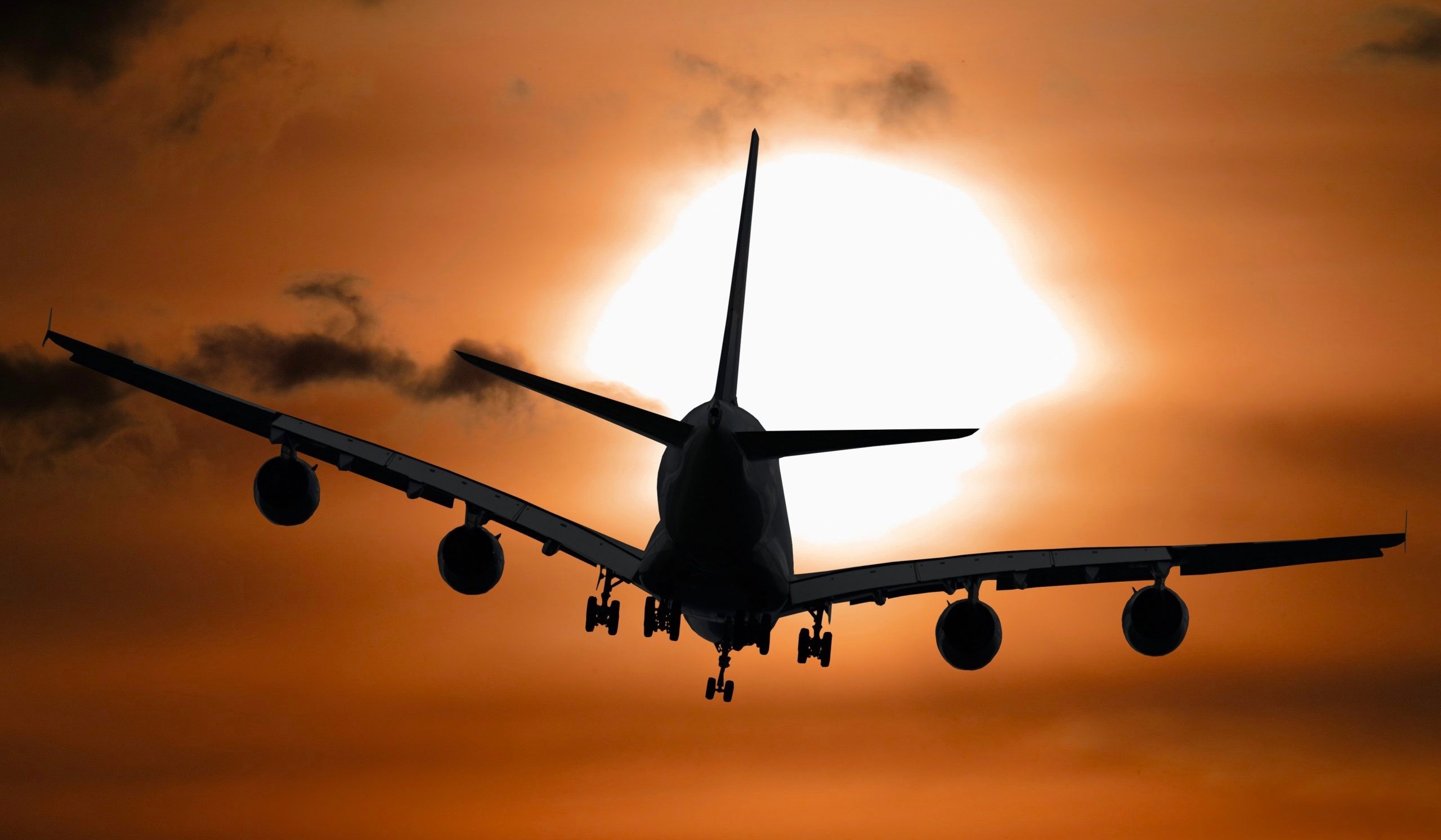 airplane flying into sunset