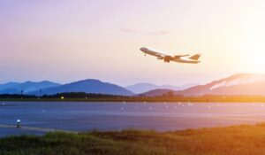 plane taking off from runway with sunset in background
