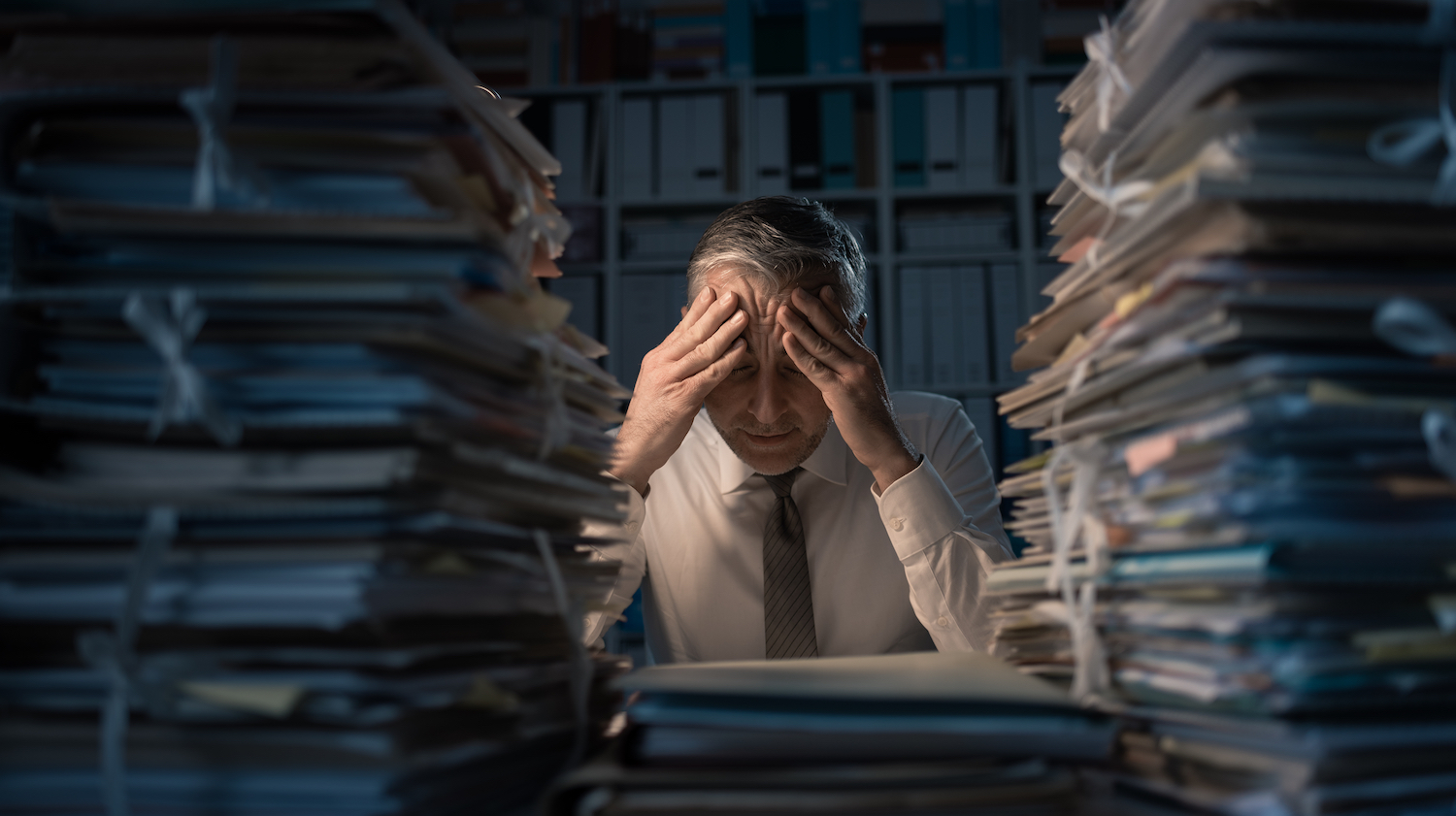 man overwhelmed with lots of data to review