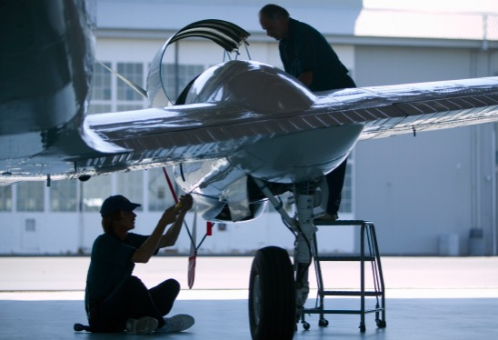 Aircraft in hangar with two aircraft maintenance technicians working on it