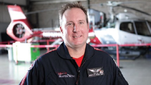 Nick King Director of Maintenance Hospital Wing in Hangar with Helicopter