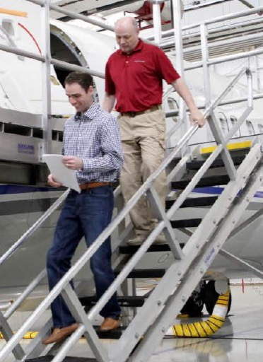 Robert Everett Chief Inspector & Director of Quality Hillwood Airways walking down Hangar stairs