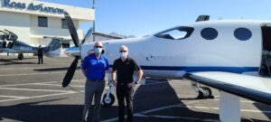 Tim Taylor and Doug King (CEO of Epic Aircraft) standing outside with an Epic Aircraft E1000 GX aircraft in background.
